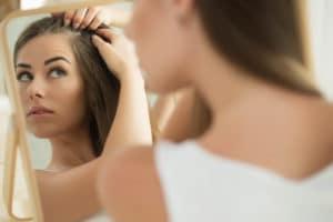 Женщина осматривает волосы