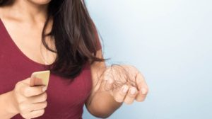 Женщина с расческой в руках на которой выпавшие волосы