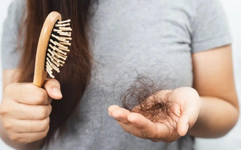 Женщина с расческой и выпавшими волосами в руке